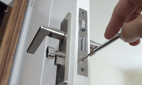 a locksmith opening a door hinge