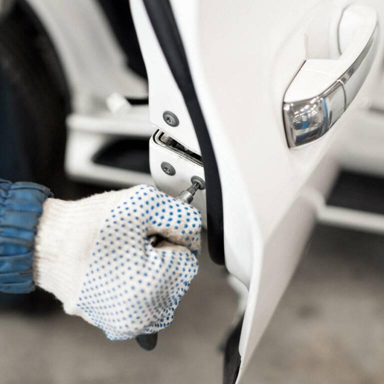 locksmith car will repair white car door , selective focus to screwdriver.